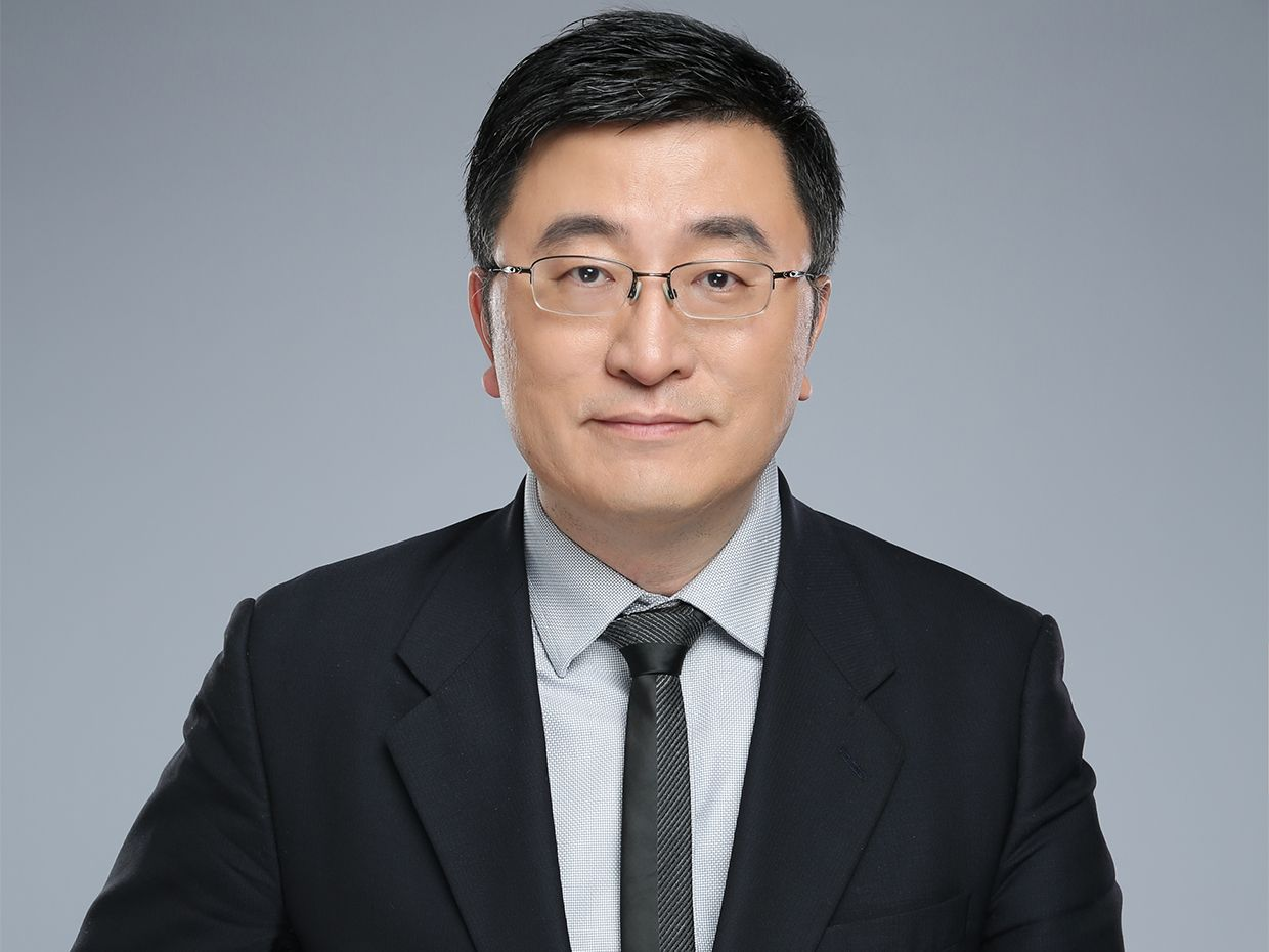 An image of Chenyang Xu on a gray background looking directly into the camera.