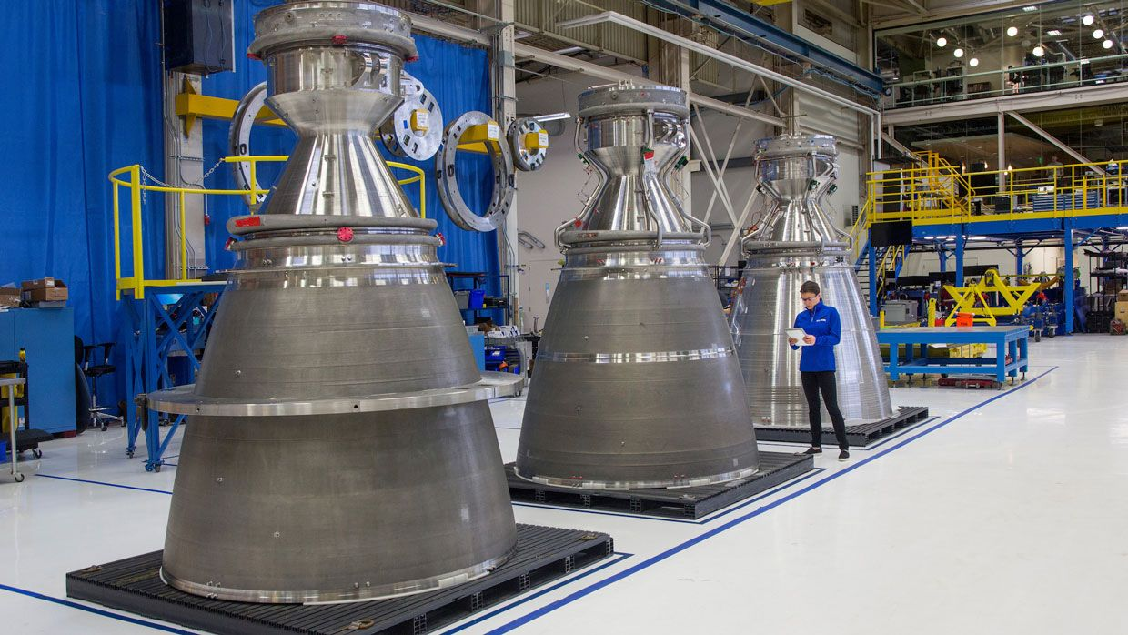 A Blue Origin worker inspects these giant nozzles destined to become part of the company's new BE-4 rocket engines.