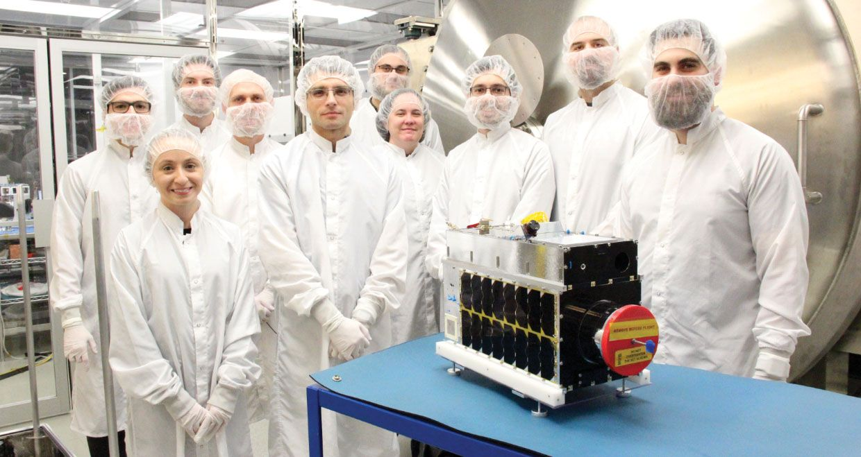 Photo of people in gowns in front of a satellite.