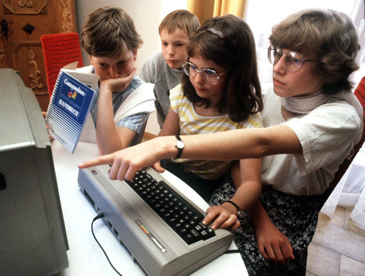 Photo of four children looking at a Commodore computer screen.