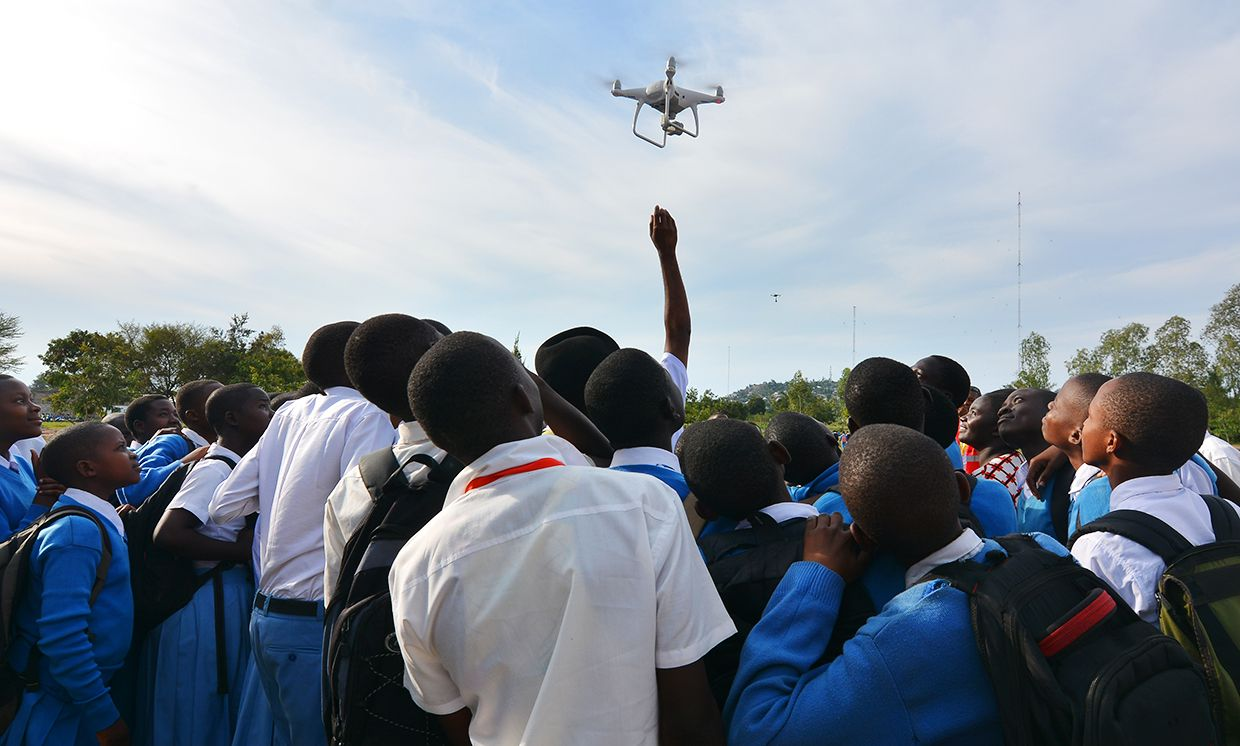 Photo showing students looking up at flying drone.