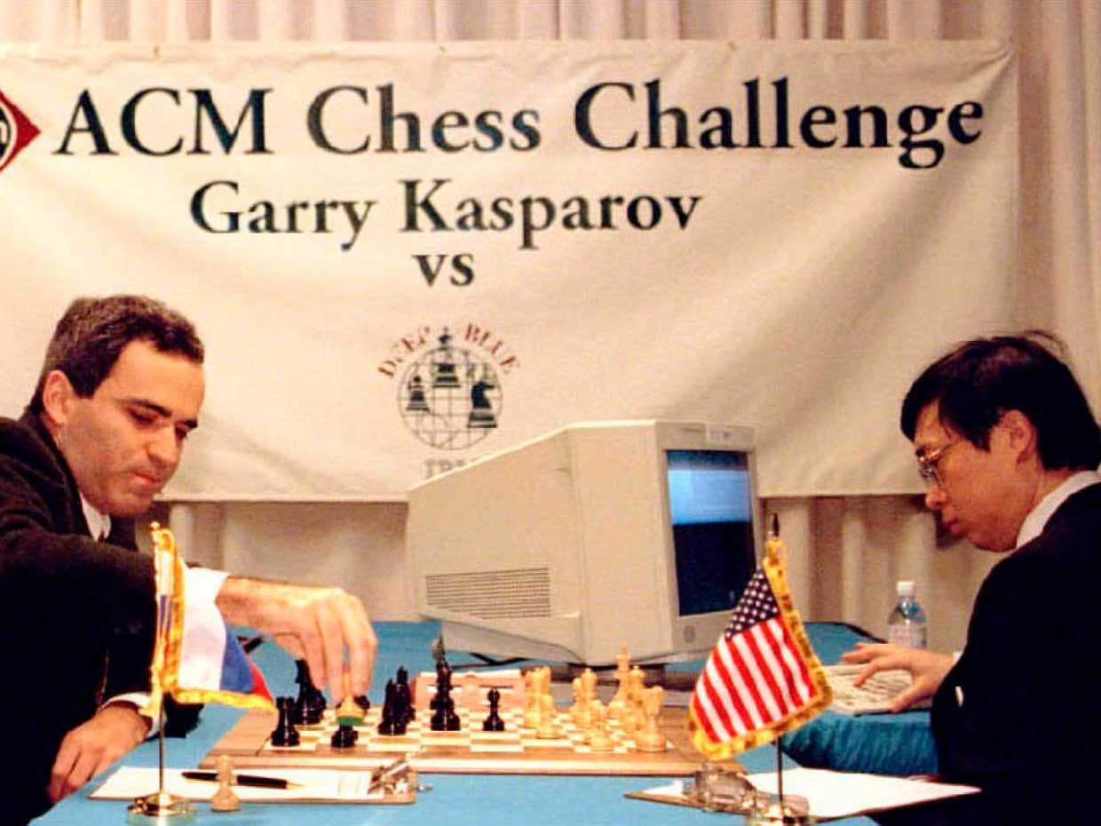 Photo of a man playing chess and a man sitting next to a computer.