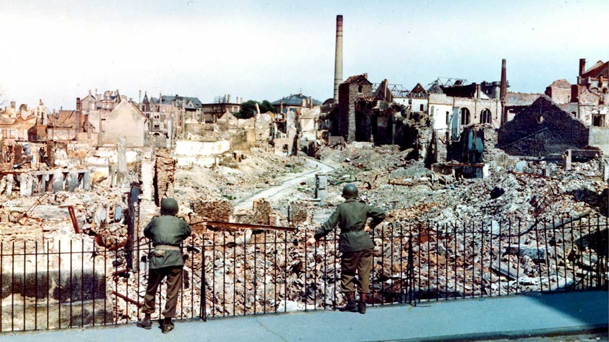 Two American soldiers stand behind a fence and survey the damage sustained during a saturation bombing raid on the city of Darmstadt, Germany, 1945. The raid, conducted on September 11 & 12, 1944 by British Royal Air Force Bomber Command, resulted in thousands of deaths, and rendered more than half the city's inhabitants homeless.