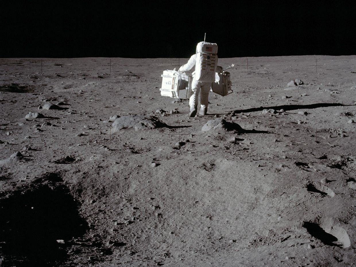 On the moon, Apollo 11 ­astronaut Buzz Aldrin carries research equipment to the deployment area in the Sea of Tranquility.