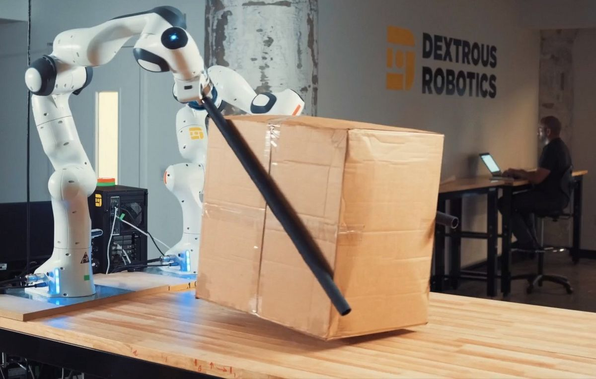 A pair of white robot hands each have a black tube attached. The tubes are pressed against the sides of a cardboard box to lift it.