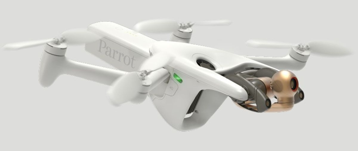 A white quadcopter with a bulbous frontend and a gold-colored camera mounted on a grey gimbal