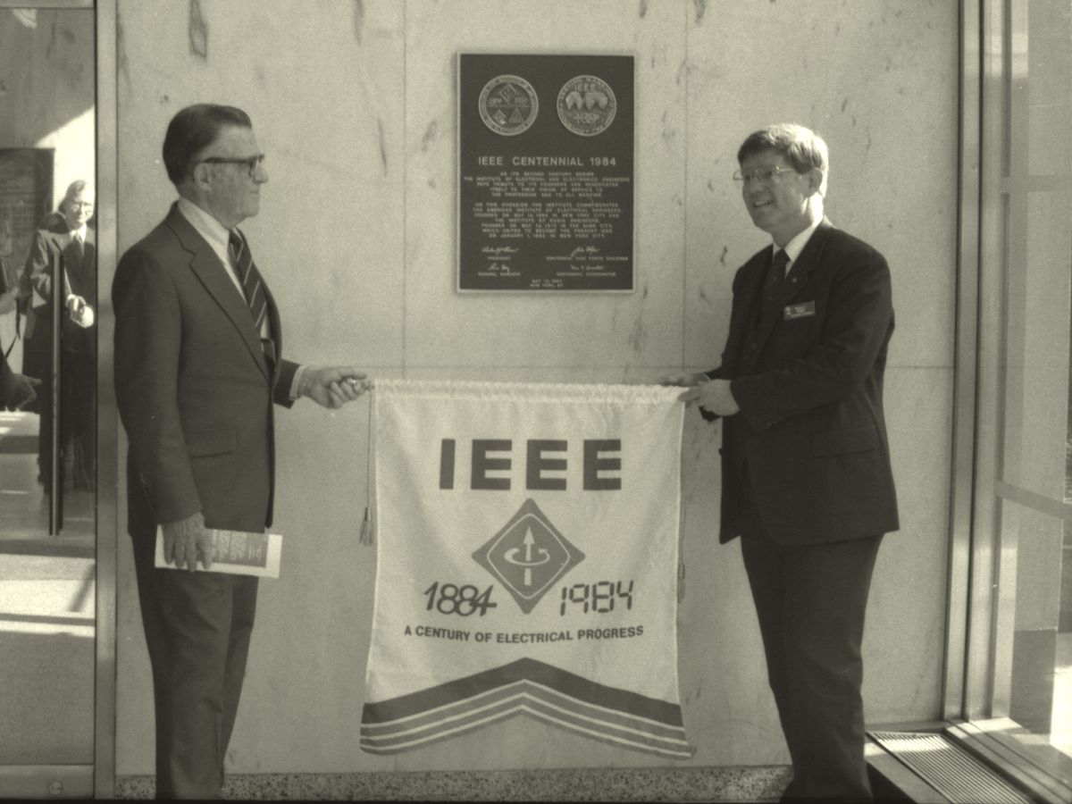 Two men standing by a plaque.