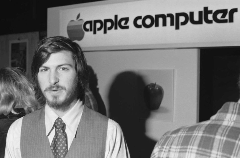 Photo of Steve Jobs in front of an Apple Computer sign