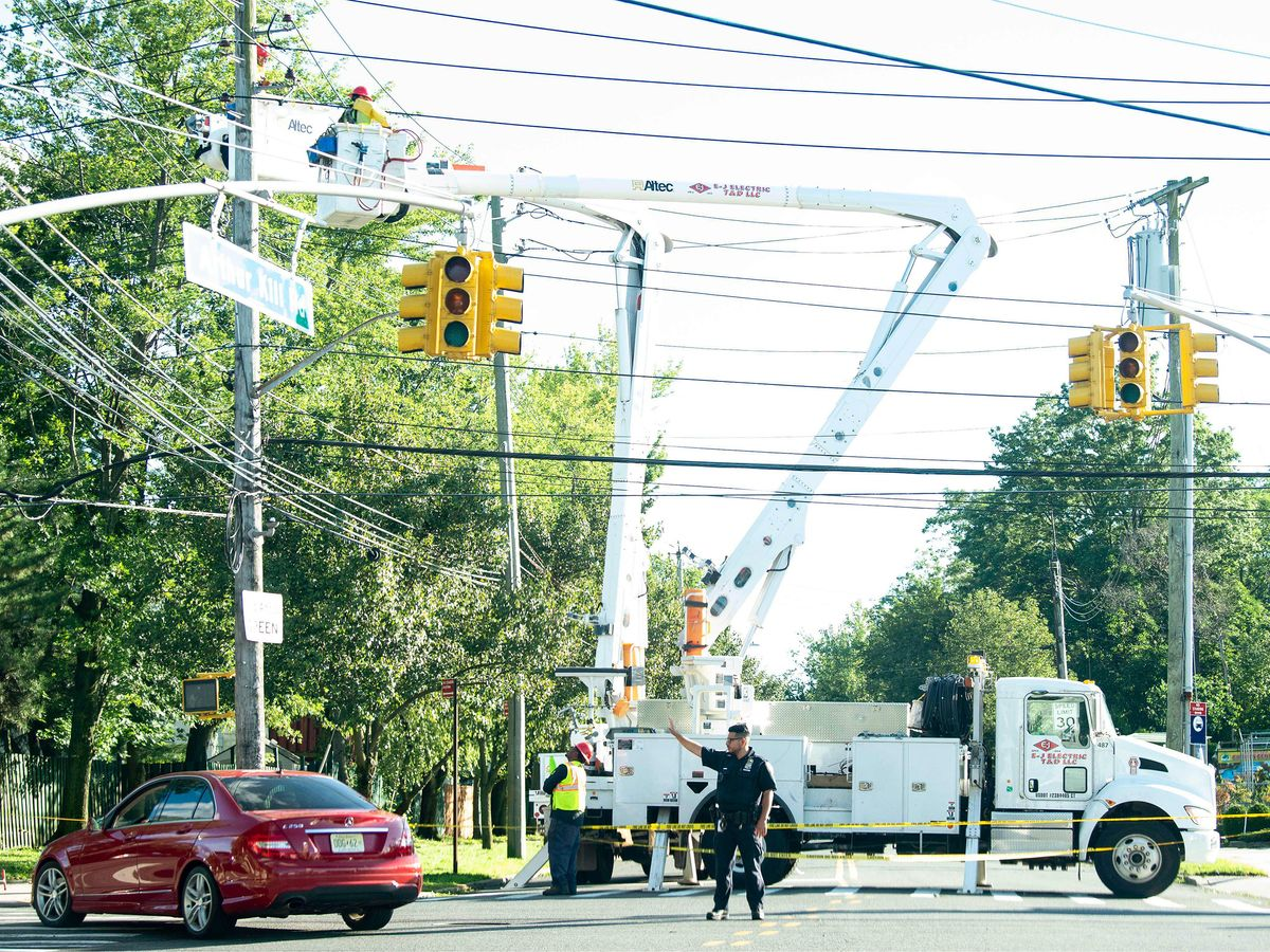 A police officer directs traffic as a Con Edison crew works to restore power due to Tropical Storm Isaias in Staten Island, New York.