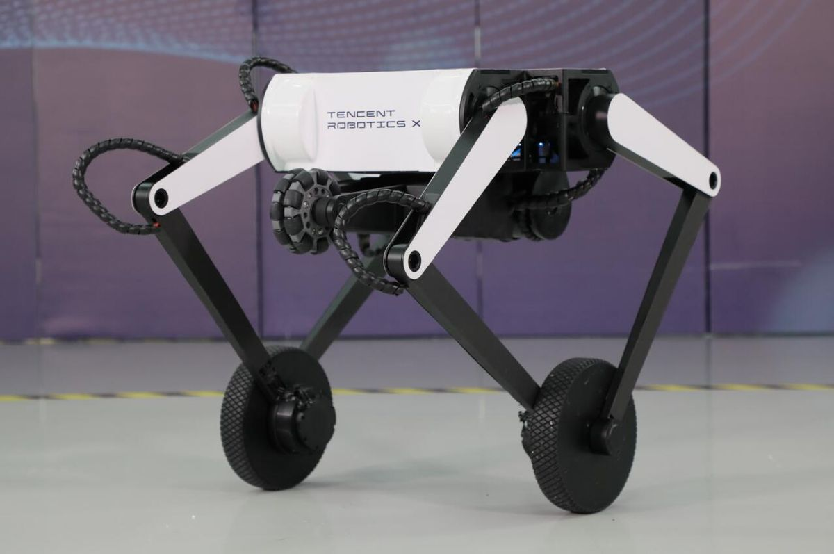 A black and white robot with four legs: each pair of legs is joined by an axle supporting a wheel. A wheeled tail is tucked up under the body.