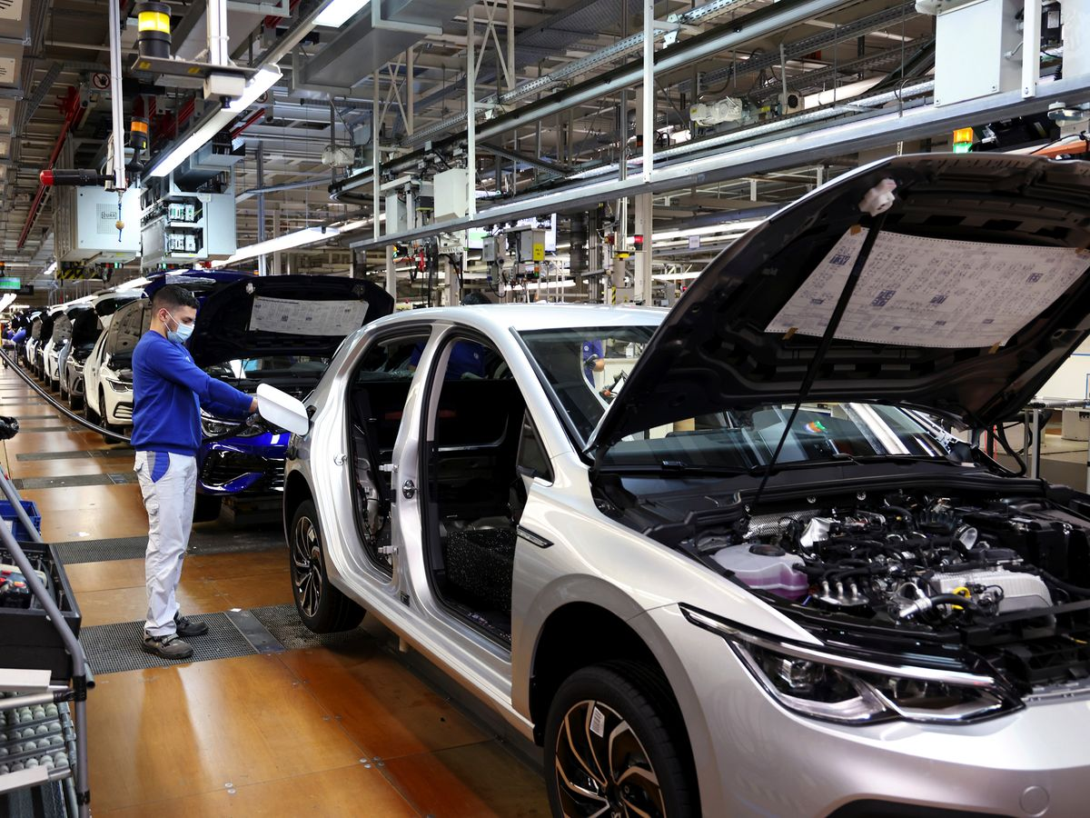 A worker fuels a Volkswagen Golf 8 automobile on the assembly line.