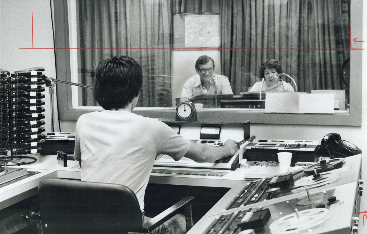 One of about 100 volunteers working for the Radio Reading Service-about 75 of them on-air readers-john Tickell reads news item from The Star along with staff member Jacqueline Donaldson from a basement studio in Oakville's Woodside Public Library.
