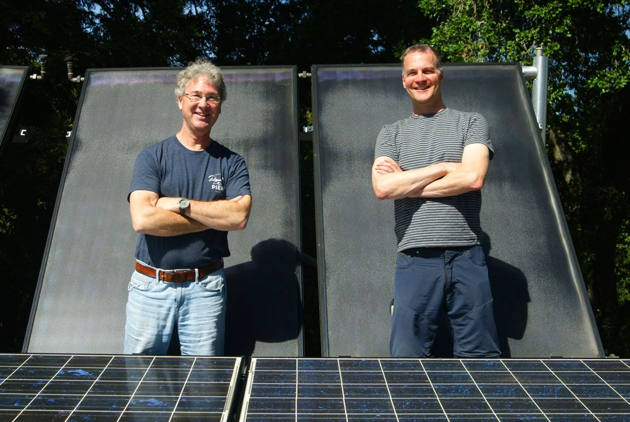 Two men standing in front of a solar panel.
