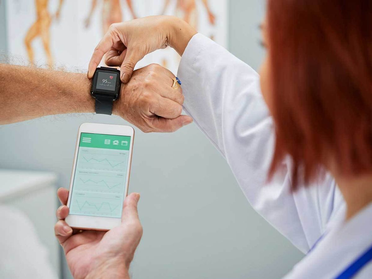 Photo of a woman holding a smart watch and a hand holding a smart phone
