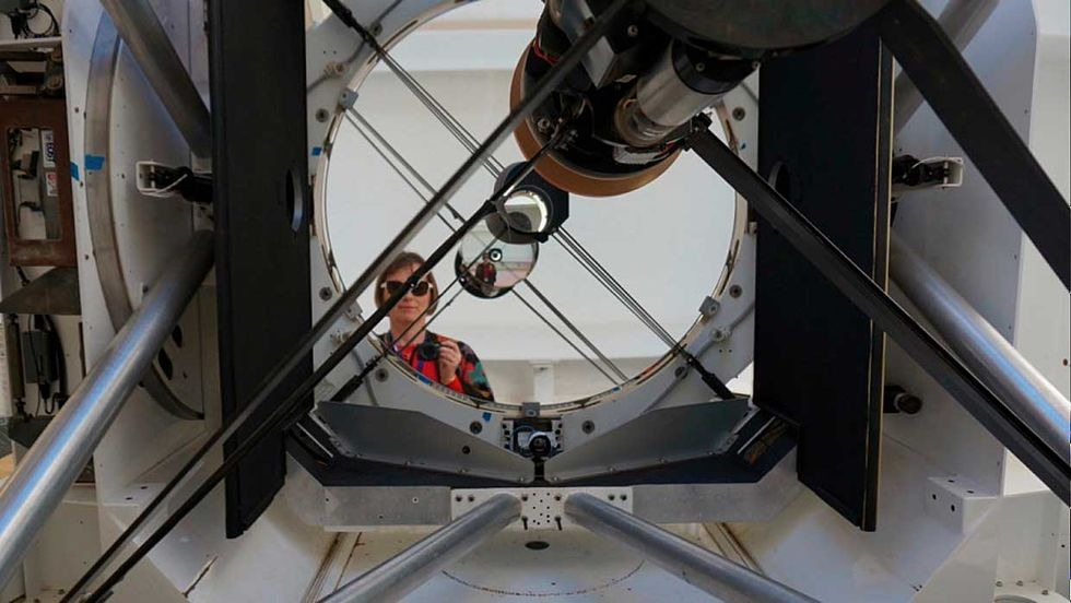 ANU instrument scientist Celine d'Orgeville stands in front of the EOS 1.8 meter telescope at Mount Stromlo Observatory.