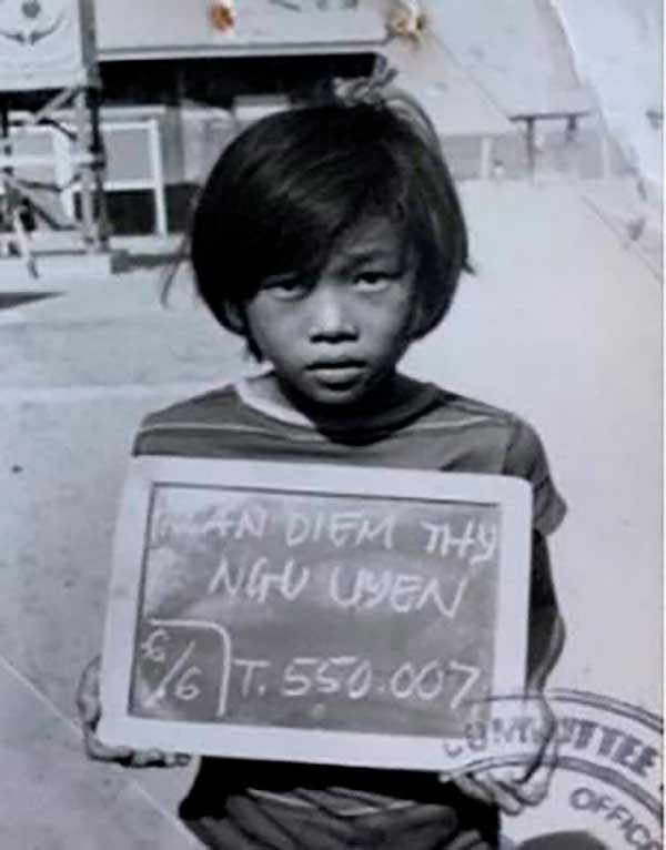 Thy Tran holding a board with her name and refugee number in Lumpini, Thailand in 1979.