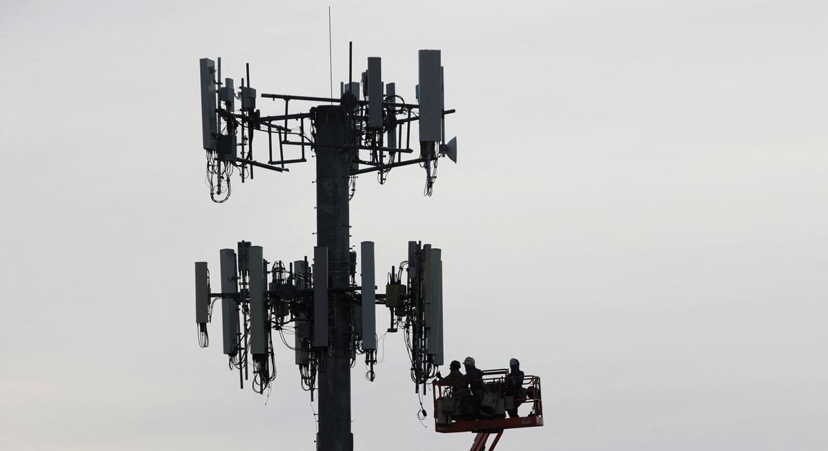 Image of workers working on a cellular tower.