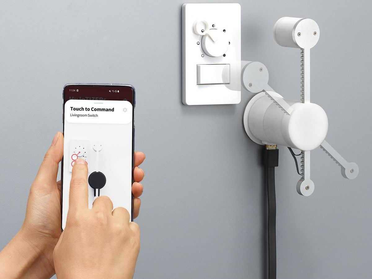 A hand holding a smartphone demonstrates an IoTIZER installed on dimmer switch