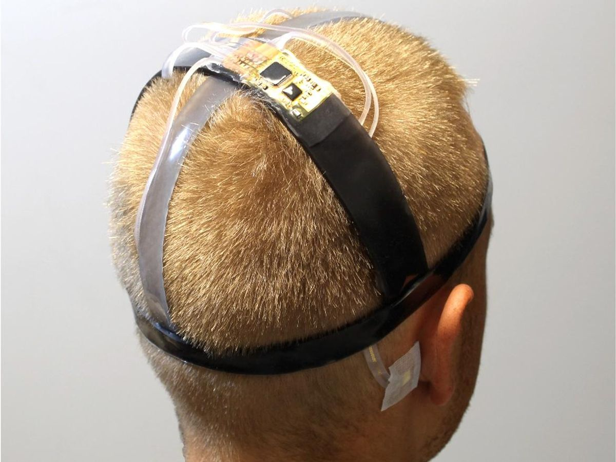 Two cross straps meet at the crown of a head, where a circuit board is placed. Another strap circles the head.
