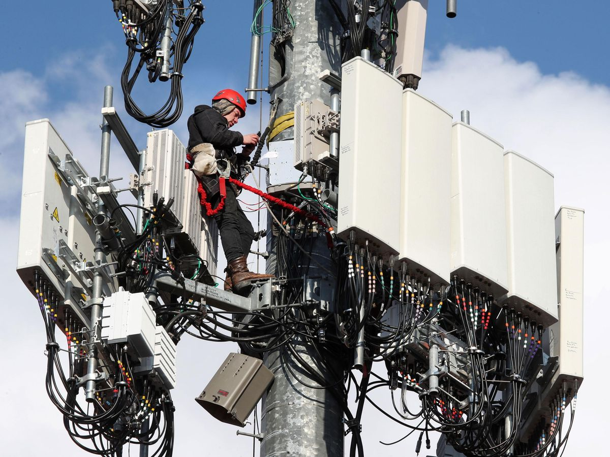 A worker rebuilds a cellular tower with 5G equipment in Orem, Utah.