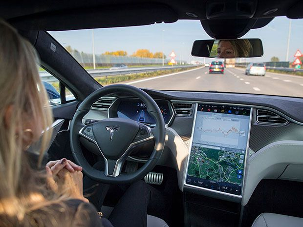A woman in a Tesla car on Autopilot without her hands on the wheel.