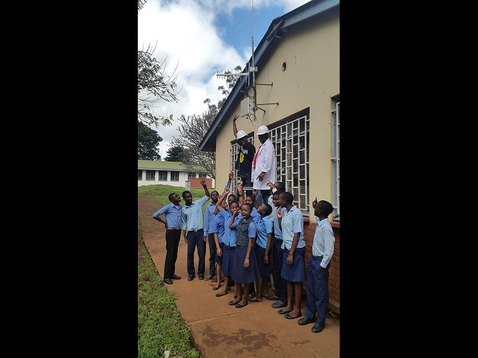 Mikeka and Jonathan Pinifolo of the Malawi Communications Regulatory Authority celebrate with students at Mulanje Secondary School after the 2015 installation of a TV white space network.