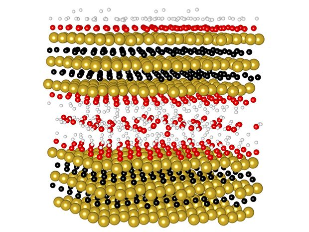 Schematic illustration of MXene structure looks like layers of gold balls with smaller black balls and some red and white balls in between the layers