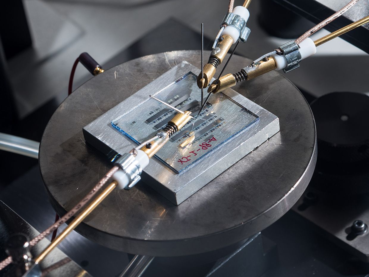 Photograph of organic-thin film transistors with a nanostructured gate dielectric under continuous testing on a probe station.