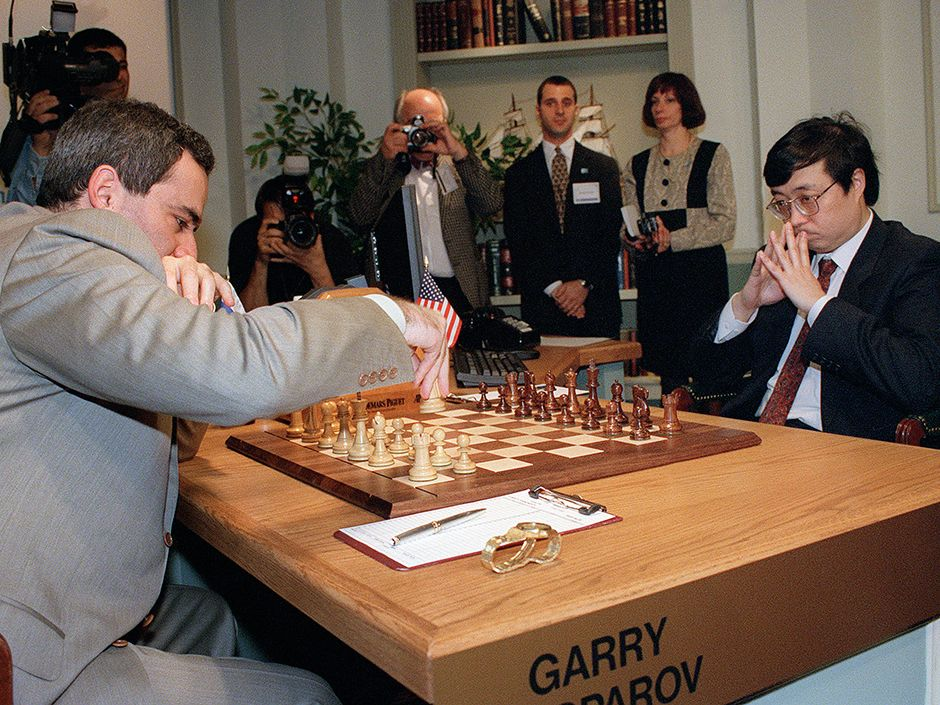 Kasporov opens a game against Deep Blue 2 in May 1997 by moving his knight. Opposite him is Feng-hsiung Hsu, moving on behalf of IBM because the company was clearly too cheap to build a cool/scary robot with an arm.