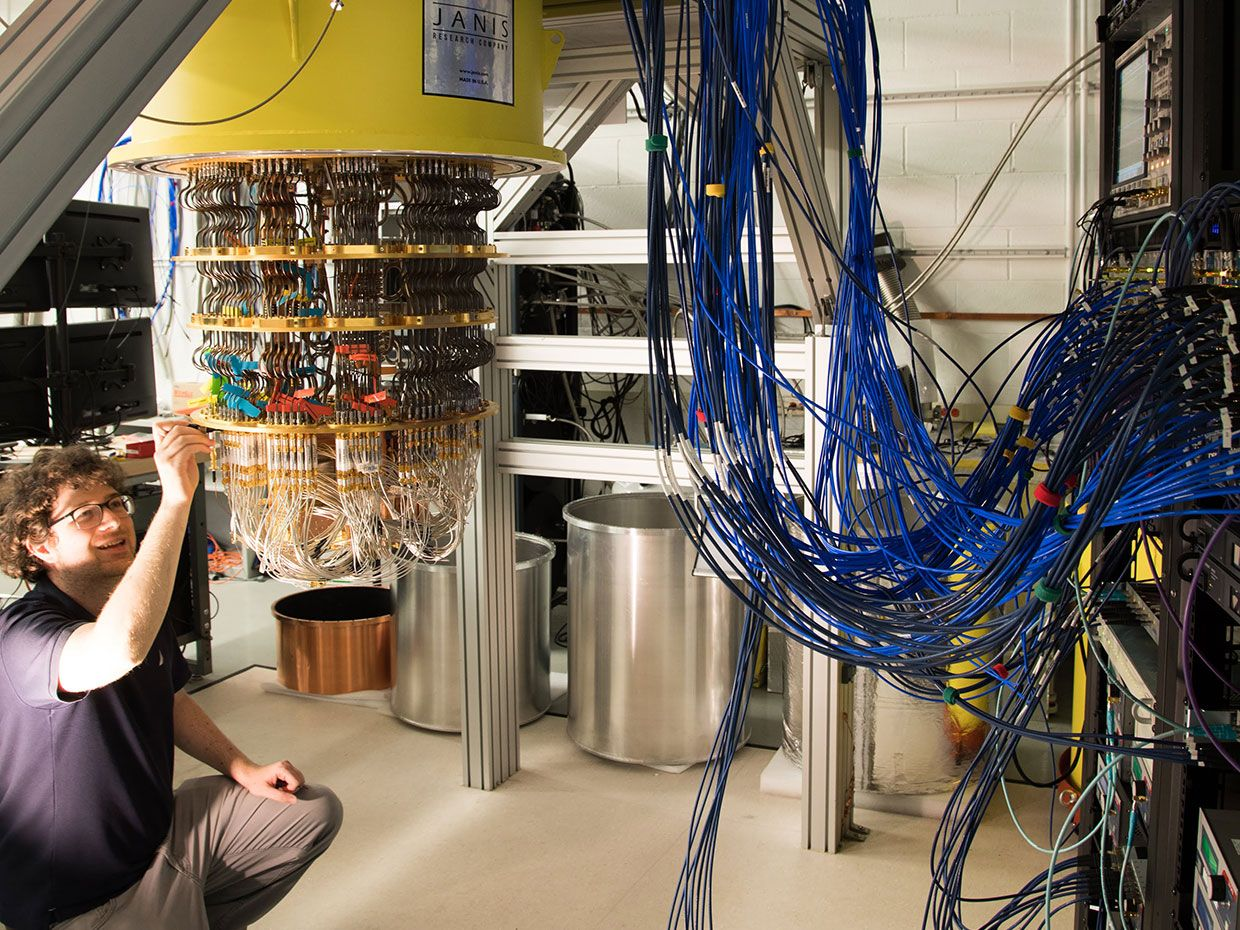 Google engineer Amit Vainsencher examines his company's quantum computer system. Even with only half the needed connections attached, there's a crowd of cables feeding into the 72-qubit quantum processor.
