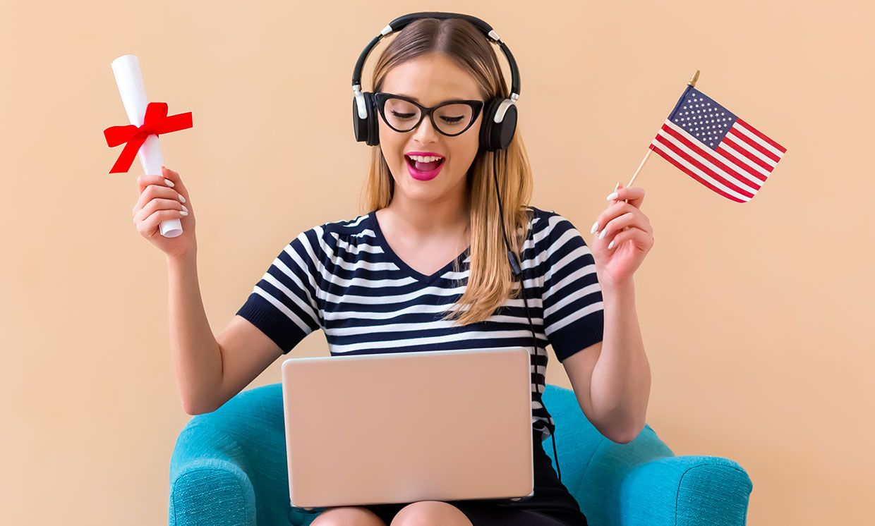 Photograph of a woman with a computer on her lap holding a diploma and a United States flag.