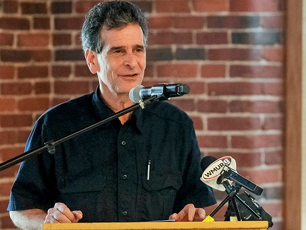 Dean Kamen, dressed in a black button-down shirt, speaking at a lectern