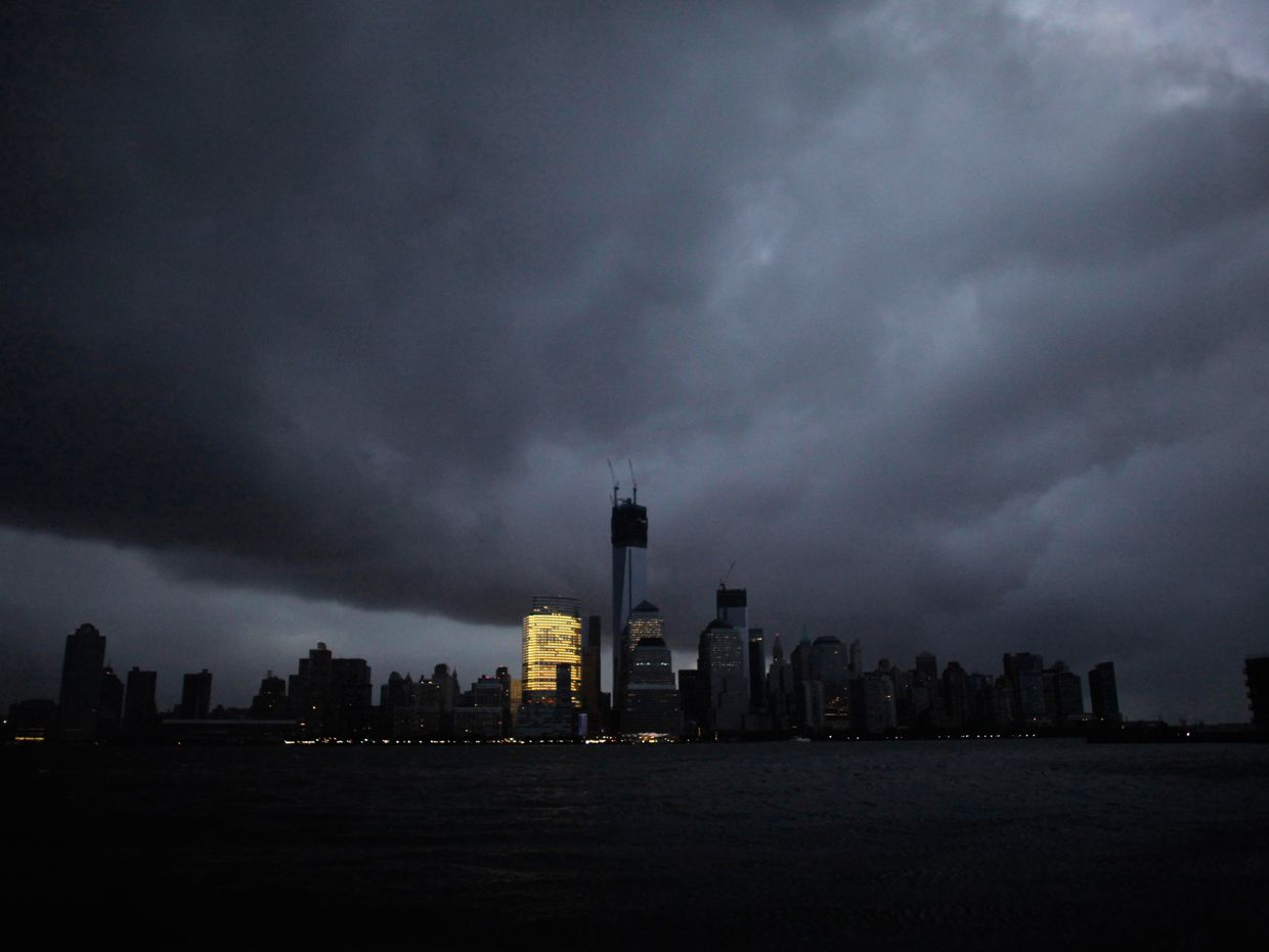 The skyline of lower Manhattan is mostly dark except for one office building after a blackout caused by Superstorm Sandy on 30 October 2012.