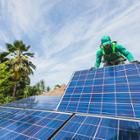 Photo of a SolarCity worker installing photovoltaic panels on a house in Hawaii.