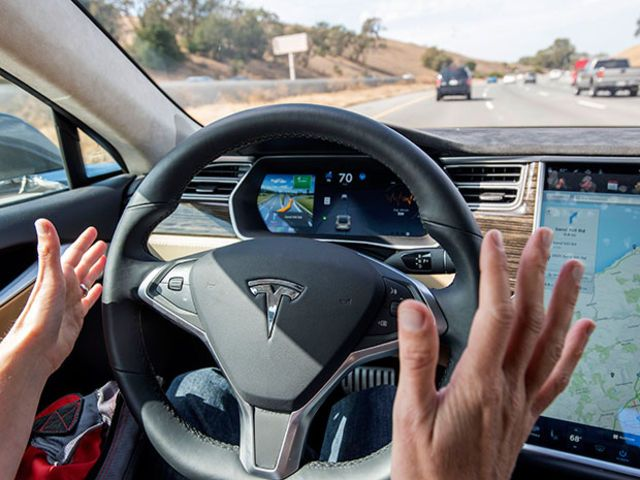 Interior view of the dashboard on a self-driving car driving on a road; the driver's hands are off the wheel