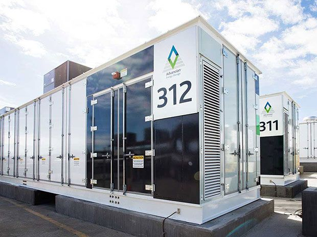 Two utility-scale energy storage units as deployed at a substation in California look like white and black cargo containers on cement pedestals