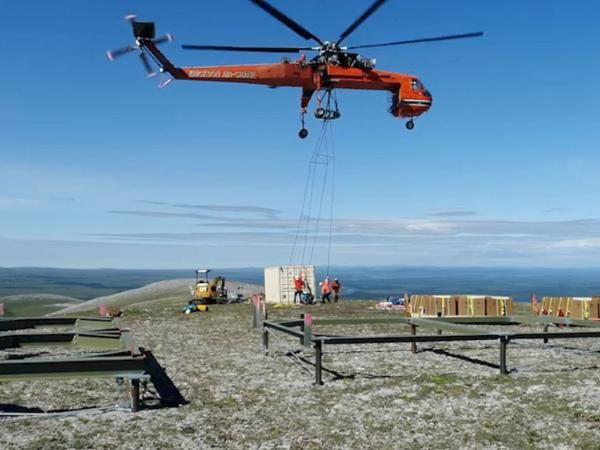 A photo of a crew of workers unloading a large box of supplies from cables attached to a helicopter above, surrounding by mountains and wilderness.