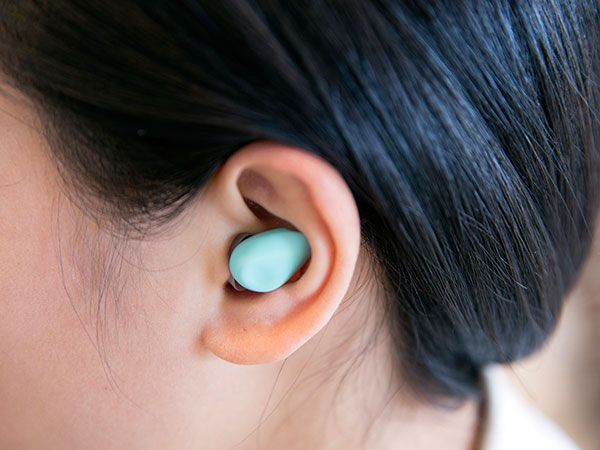 Photograph of the Yono wearable in a woman's ear.