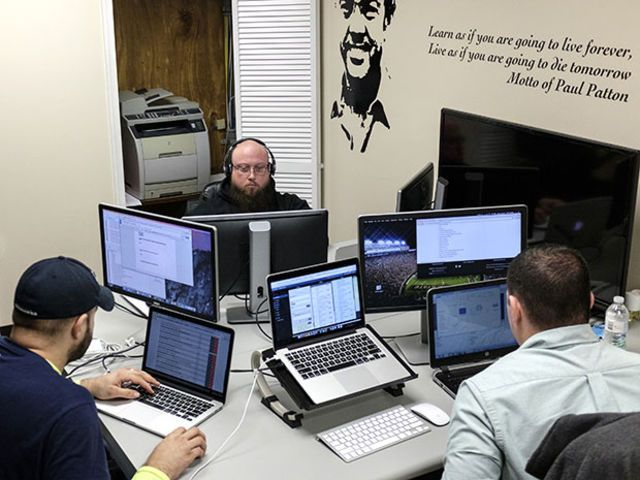 Software coders William Stevens, from left, Michael Harrison, and Brack Quillen work on computers at the Bit Source LLC office in Pikeville, Kentucky, U.S., on Monday, Feb. 1, 2016.