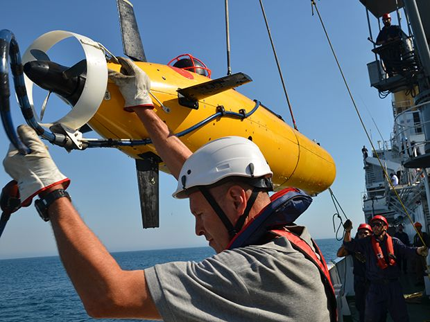 A man in a helmet lowers a yellow torpedo-shaped submersible over the side of a boat