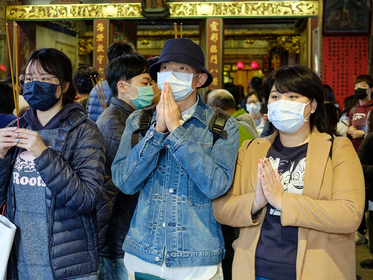 February 23, 2020 photo in Taipei, Taiwan shows people wear surgical masks in a temple.