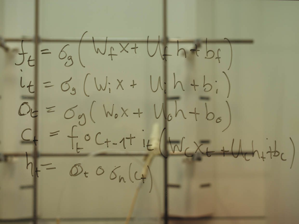 A photo shows equations drawn on a transparent blackboard.