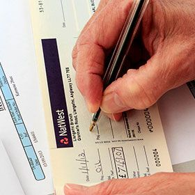 Photograph of a senior in the UK signing a check.