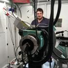 Chris Takacs stands behind X-ray topography diffraction measurement device