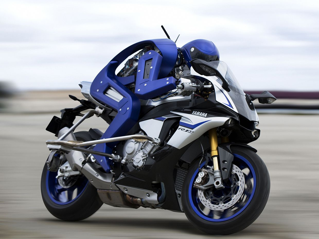 Black Motorcycle By Yamaha With A Blue Robotic Driver Named Motobot Bent Over The Handlebars