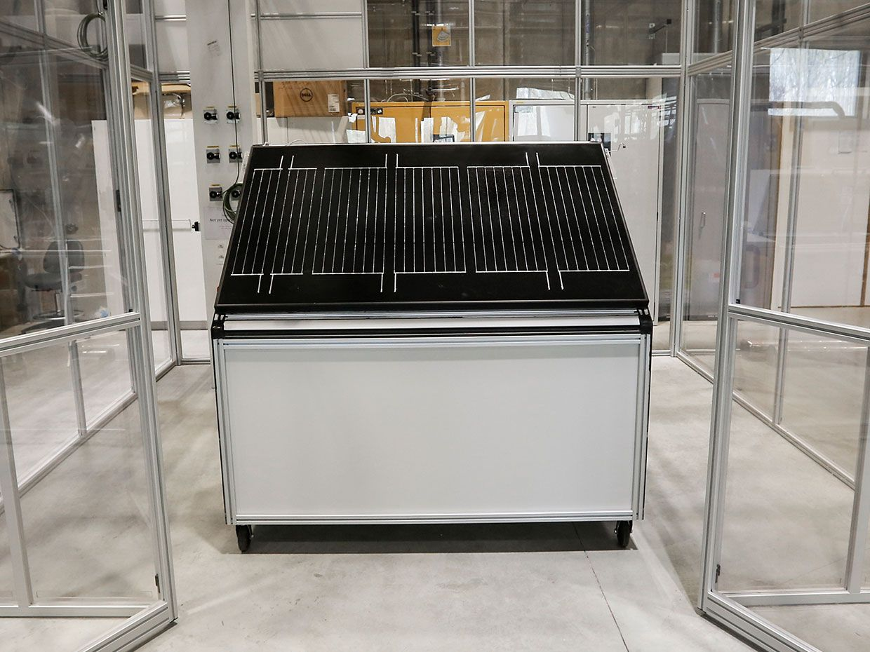 A solar panel sits in the middle of a glass enclosure in a laboratory.