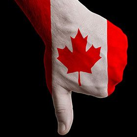 Photograph of someone giving a thumbs down, with the Canadian flag painted on their hand.