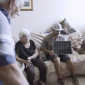 A photo shows a man sitting on a couch holding a solar charger in front of residents at a senior center.
