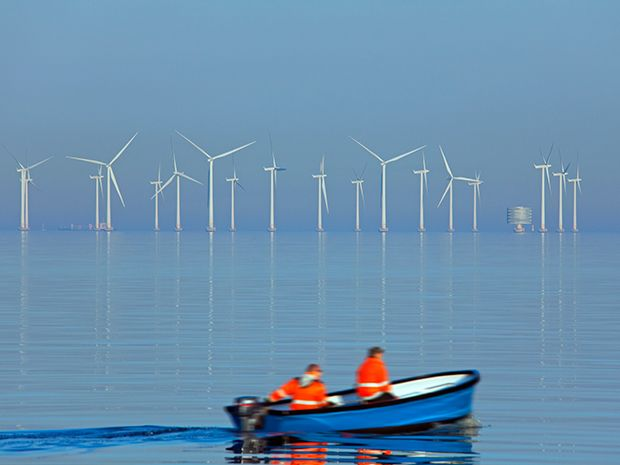 A small boat goes past the Lillgrund offshore wind farm