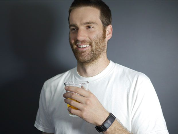 Bearded man with beer in hand and BACtrack alcohol biosensor on wrist.